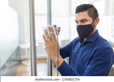 Business man wearing face mask because of Covid-19 with disinfectant cleaning glass in office