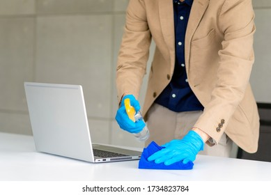 Business man wearing mask and using personal sanitizer to cleaning his hand and his table in office to keep hygiene.Preventive during the period of epidemic from coronavirus or covid19.