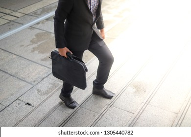 A business man wearing a suit, carrying a bag, walking up the stairs Means progress to success