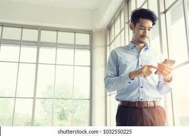 Business man wearing suit, looking smartphone. Open space loft office. Panoramic windows background.