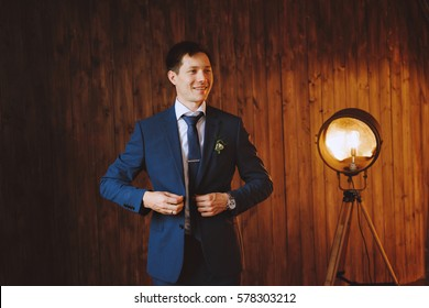 Business man wears blue jacket. The groom. In the background is a retro lamp. The walls are of dark wood