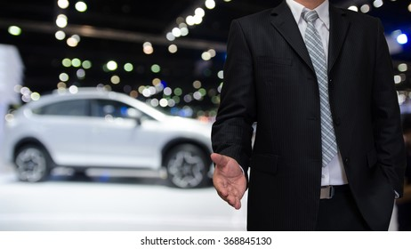 business man with welcome hand on blurry motor show background