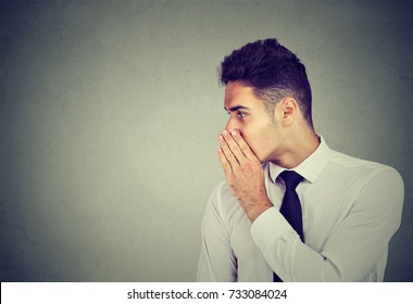 Business man whispering a gossip secret to someone isolated on gray background