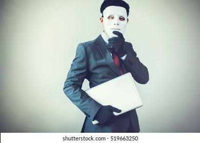 Business man in white mask wearing gloves and stealing computer and digital information - fraud, hacker, theft, cyber crime concept.