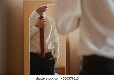 The business man in white shirt and tie looks at himself in the mirror