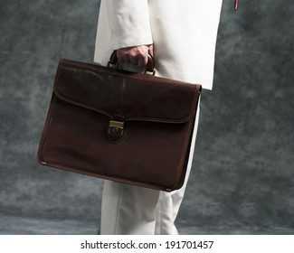 business man in white suit holding briefcase