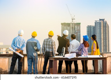 Business man who point to target and engineer team at construction site and city scape background.