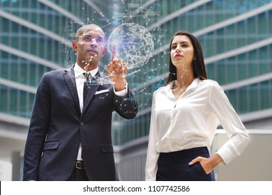 A business man and woman of different ethnicities talk about finance looking at holographic and futuristic graphic on the performance of economic markets and banks. Concept of: success, future and tea