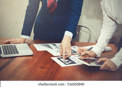 Business man and Business woman discussing and pointing at financial and strategy documents with laptop during business meeting