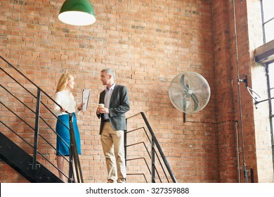 Business man and woman discussing work on way to meeting in convered loft apartment