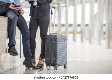 Business man and woman  Dragging suitcase luggage bag,walking to passenger boarding in Airport,travel to work.Asian tourist men and women  wearing black suit pull trolley bag. Business travel concept