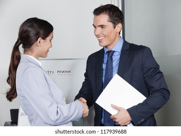 Business man and woman giving handshake in the office