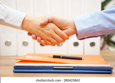 business man and woman are handshaking over documents in with office in background