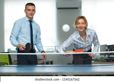 Business man and woman are playing together in table tennis. Play in the team. Office games during a working break. Office entertainment.