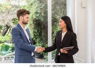 Business man and woman shaking hand after job success