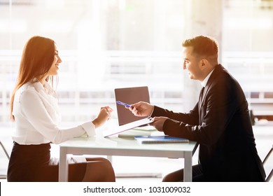 Business man and business woman sign a contract. Satisfied with loan terms woman singing contract when sitting at desk in front of male bank employee at office.