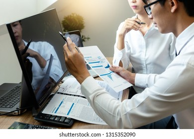 business man and woman sit at the table looking at computer laptop in the office , they talking about stock market invest or talk with customer