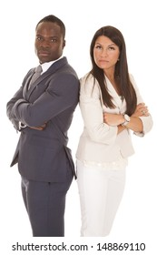 A business man and woman standing back to back with serious expressions on their faces.