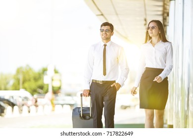 The business man and woman in sunglasses walk with a suitcase