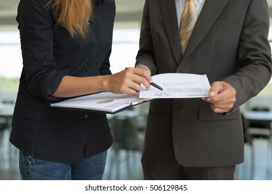 Business man and woman talking about financial report in office.
