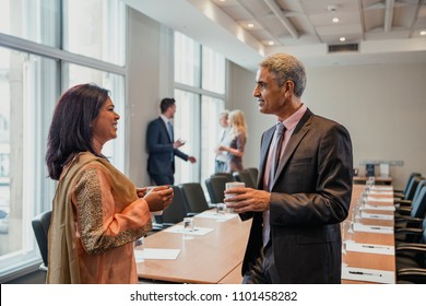 Business man and business woman talking before the meeting starts. Being friendly and talking, getting to know each other.