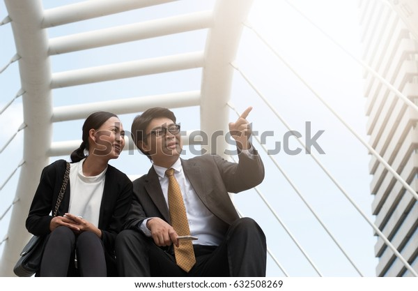 Business man and woman talking with building background