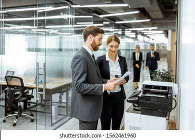 Business man and woman talking near the copier during a coffee break in the hallway of the big corporation