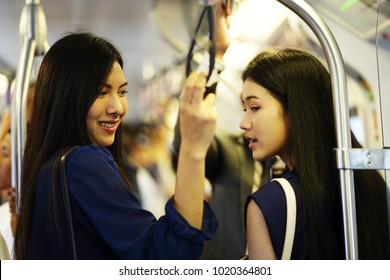 ?Blur: The business man and woman travel by subway train in the morning time. woman hand holding onto a handle of bus or subway train (blur background). Young Man and woman standing and holding handle