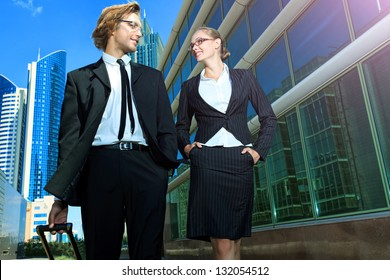 Business man and business woman are walking the streets of the big city.