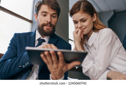 business man and woman watching tablet
