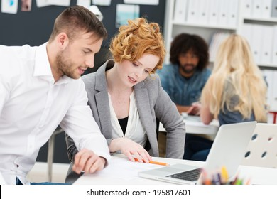 Business man and woman at work in the office pouring over paperwork on a desk together with multiethnic colleagues working in the background
