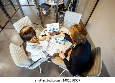 Business man and woman working with charts and graphics, while sitting at the round table in the meeting room, view from above