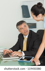 Business man and woman working on a laptop and a digital tablet