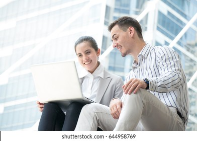 Business man and woman working on laptop together on building background in city outdoor feeling happy