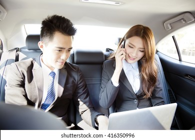 Business man and woman working together in the car