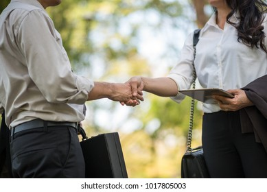 Business man and business women shake hand with partner something is interested them work at public park