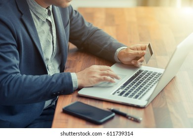 Business man work with laptop, hand on credit cards