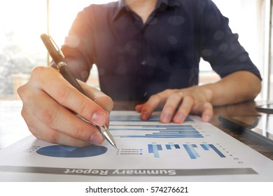 business man working with analysis graph chart document at office table - business and finance analysis concept