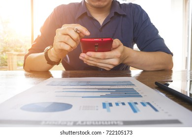 business man working with analysis graph chart document and using mobile phone at office table - business and finance analysis concept