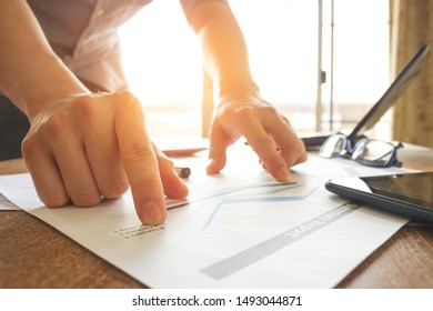 business man working and analyzing graph and chart document on office desk