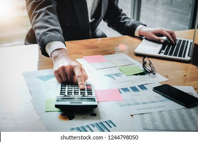 business man working with calculator and digital tablet computer with financial business strategy layer effect in office, bookkeeper and auditor concept.
