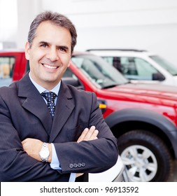 Business man working at a car dealer smiling