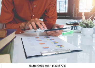 Business man working with digital tablet and book and document on wooden desk in modern office.Business analysis and strategy concept.