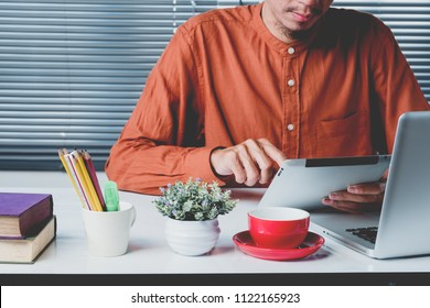 Business man working with digital tablet and laptop computer and document on wooden desk in modern office.Business analysis and strategy concept.