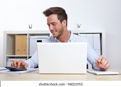 Business man working with laptop and calculator in office