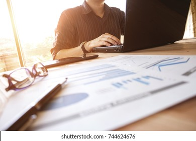 business man working with laptop computer, mobile phone, and analysis graph chart document at office table - business and finance concept