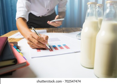 Business man working in milk bottle quality control hard job concept, quantity checking in the office, Facility layout planning in the future.
