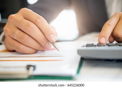 Business man working with new startup project.Hand woman holding pen pointing on summary report chart and calculate finance.discussion and analysis data the charts and graphs.