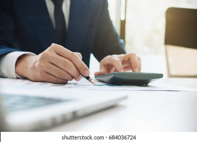 Business man working with new startup project hand pointing graph discussion and analysis data charts and graphs and using a calculator to calculate  numbers.Business finances and accounting concept