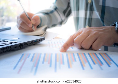 Business man working at office desk with laptop, pen, notebook and documents